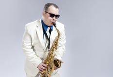 Männlicher Saxophon-Spieler, der an Alto Saxo In White Suit und an der Sonnenbrille gegen Weiß durchführt Stockfotos