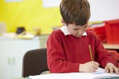Männlicher Schüler-übendes bei Tisch schreiben Lizenzfreies Stockbild