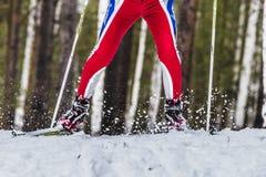Männlicher Skifahrer des Nahaufnahmefußes sprüht Schnee von unterhalb des Skis Stockfotos