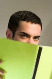 Männlicher Student, der hinter einem Buch sich versteckt Lizenzfreie Stockfotografie