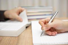 Männlicher Student ist Lesebuch, Frau schreibt in Notizbuch Stockbild