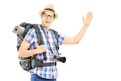 Männlicher Tourist mit dem Rucksack, der mit seiner Hand wellenartig bewegt Lizenzfreies Stockbild