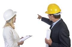 Männlicher und weiblicher Architekt, der Hintergrund betrachtet Lizenzfreies Stockfoto