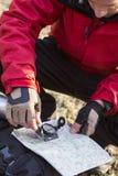 Männlicher Wanderer, der Kompass und Karte im Wald verwendet Stockbilder