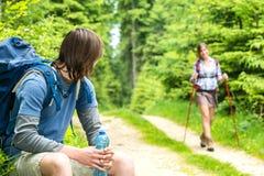 Männlicher Wanderer, der zurück schaut, wartend das Mädchen Lizenzfreie Stockfotos