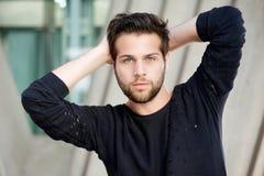 Männliches Mode-Modell, das mit den Händen hinter Kopf aufwirft Lizenzfreie Stockbilder