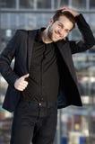 Männliches Mode-Modell, das mit der Hand im Haar lächelt Lizenzfreies Stockfoto