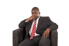 Männliches Modell im Anzug und in roter gestreifter Bindung, die im Stuhl sitzen Stockfotografie