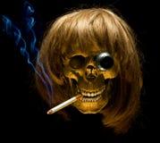 Mänsklig skalle i wig med den rökande cigaretten för monocle Arkivfoto