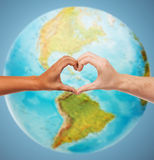 Mänskliga händer som visar hjärta, formar över jordjordklotet Royaltyfri Fotografi