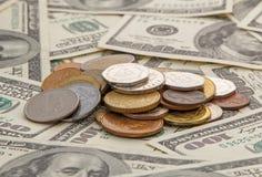 Münzen auf hundert Dollar Banknoten Lizenzfreie Stockbilder