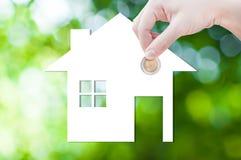 Münzen-Hand, die Hausikone in der Natur als Symbol der Hypothek, Traumhaus auf Naturhintergrund hält Stockfotografie
