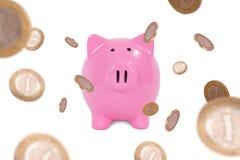 Münzen um Sparschwein Stockfotos