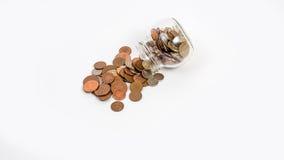Münzen verschüttet vom Glas Stockfotografie