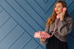 Moça à moda atrativa com o telefone cor-de-rosa retro em emoções do fundo do aqua foto de stock royalty free