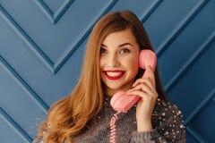 Moça à moda atrativa com o telefone cor-de-rosa retro em emoções do fundo do aqua fotografia de stock royalty free