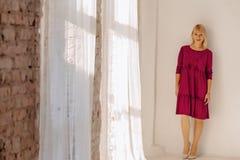 Moça à moda atrativa perto da janela no interior claro imagens de stock royalty free