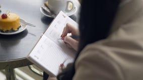 A moça à moda escreve no diário no café video estoque