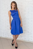 Moça à moda na moda elegante bonita com cabelo longo e composição brilhante no vestido azul que levanta para a câmera no estúdio Foto de Stock