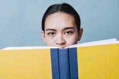 A moça é confundida que lê o livro de texto com o espaço da cópia fotografia de stock royalty free