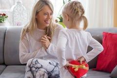 A moça é dar atual a sua mãe fotografia de stock royalty free