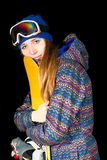 A moça abraça seu snowboard no estúdio no fundo preto imagem de stock
