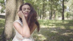Moça adorável do retrato com o cabelo moreno longo que veste um vestido branco longo da forma do verão que senta-se sob uma árvor filme