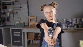 Moça adorável no avental que guarda uma carpintaria da broca dentro Retrato de uma menina com uma broca que olha a câmera video estoque