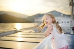 Moça adorável que aprecia o passeio da balsa que olha fixamente no mar no por do sol Criança que tem o divertimento em férias em  fotos de stock