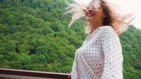 Moça adulta bonita com o cabelo de voo longo louro coberto na ponte do ferro sobre um abismo, senhora em animais selvagens magníf vídeos de arquivo