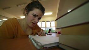 Moça afligida que trabalha na biblioteca video estoque