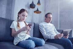 Moça agradável que joga em seu smartphone imagem de stock royalty free