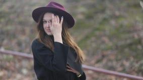 A moça alegre elegante com cabelo longo, o chapéu roxo e o revestimento preto anda abaixo da rua Tempo ventoso nebuloso video estoque