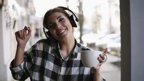 Moça alegre, engraçada que escuta a música nos fones de ouvido e que dança com uma xícara de café disponivel Rua borrada video estoque