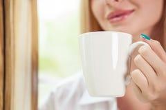 A moça alegre está bebendo o café quente Fotos de Stock Royalty Free