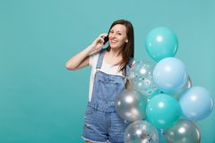 A moça alegre que fala no telefone celular que conduz a conversação agradável que comemora guarda balões de ar coloridos foto de stock royalty free