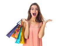 A moça alegre realiza em sua mão muitos pacotes bonitos e os risos são isolados no fundo branco Fotos de Stock