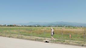 A moça anda ao longo da cerca farpada do aeroporto Batumi, Geórgia filme