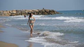 A moça anda ao longo da praia da costa de mar no movimento lento video estoque