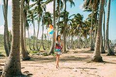 A moça anda na praia Entre as palmas fotografia de stock