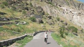 A moça anda no monastério Vardzia - Geórgia da caverna video estoque