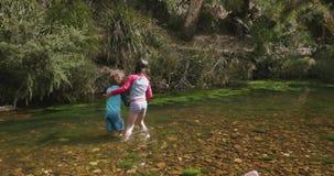 A moça apoia um menino novo enquanto andam o joelho profundamente na água em um rio video estoque