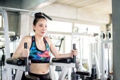 Moça asiática que aquece-se com pesos no health club do Gym foto de stock
