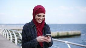 A moça atrativa com hijab em sua cabeça está sorrindo ao texting a alguém e ao enrolar algo nela filme