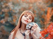 A moça atrativa com jogos vermelhos impetuosos do cabelo reto com seu animal de estimação, princesa do duende joga a fada animal  imagem de stock royalty free