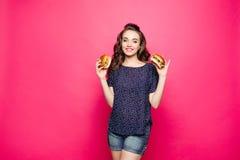 Moça atrativa com o cabelo moreno longo que guarda dois hamburgueres sobre o fundo cor-de-rosa imagem de stock royalty free