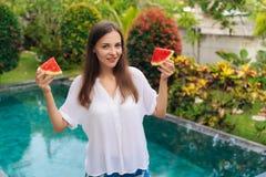 Moça atrativa do retrato que guarda duas fatias de melancia suculenta em suas mãos perto da associação imagem de stock royalty free