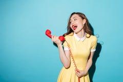 Moça atrativa no vestido que fala no tubo retro do telefone Foto de Stock