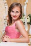 A moça atrativa no vestido vermelho está estando Fotografia de Stock