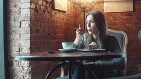 Moça atrativa que come um bolo que senta-se em uma tabela em uma casa do café ou do café video estoque